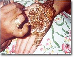 A mehendi (henna) artist applying mehendi to Jasmine Patel's hand.